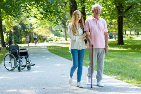 Jonge vrouw helpen oudere man met het lopen met riet in het park Stockfoto - 78749919