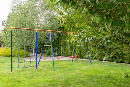 Tuin in de speeltuin voor kinderen met een schommel, omgeven door bomen