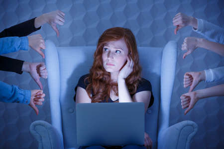 criticized: Lonely young girl with laptop criticized in internet Stock Photo