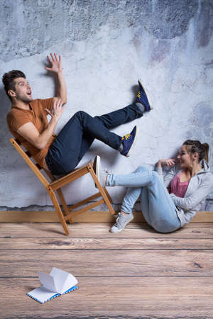 Girl knocking the chair with man falling down Stock Photo