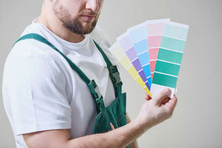 Jonge man die tegen grijze muur staat, overalls draagt en kleurstalen houdt Stockfoto