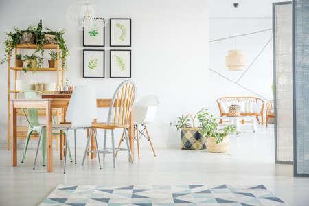Witte kamer met gemeenschappelijke tafel, stoelen en boekenplank