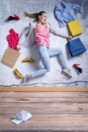 Jonge vrouw omringd door nieuwe kleding en schoenen