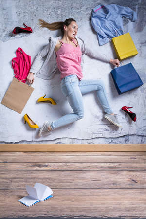 Young woman surrounded by new clothes and shoes