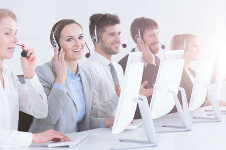 salespeople: Business group with headsets working in call center