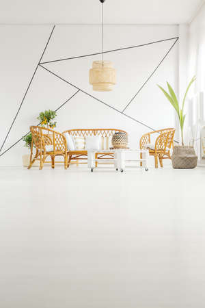 open floor plan: White living room with rattan furniture and decorative wall tape