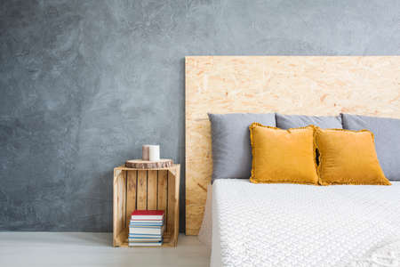 Wooden box as a nightstand by the wooden modern bed Zdjęcie Seryjne
