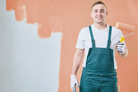 Young painter standing against orange wall and holding a roller Stock Photo