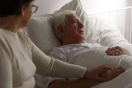 Elderly woman holding senior husbands hand in last moments in hospital Stock Photo