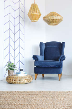 White room with decorative wall tape, blue armchair, lamp, pouf
