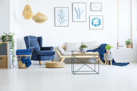 White living room wih navy blue armchair, sofa and posters