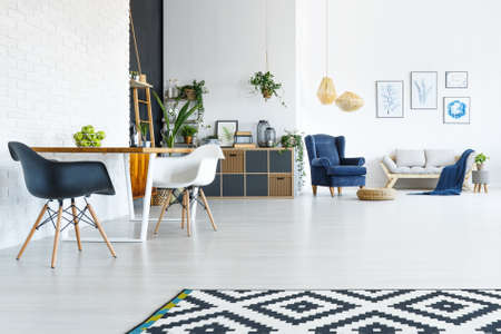 Wit appartement met een houten tafel, stoelen en een open woonkamer