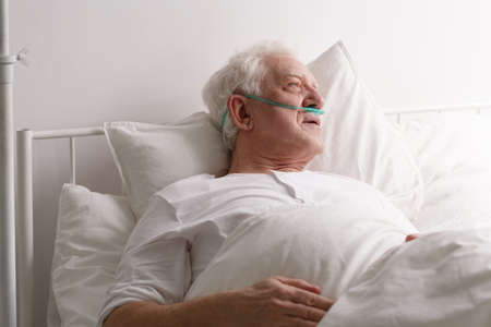 Sick elderly dying man in hospital bed looking out window Stock Photo