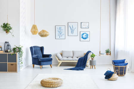 Witte woonkamer met houten bank, blauwe leunstoel, lampen, posters