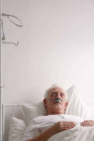Worried elderly male patient thinking while staring at hospital ceiling