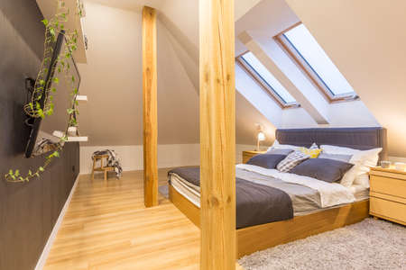 attic: Double bed in stylish wooden bedroom in the attic