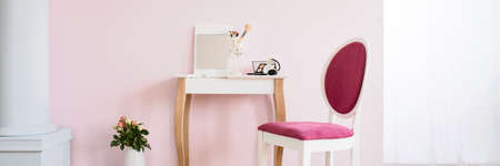 apartment: Small dressing table and pink chair in white and pink room