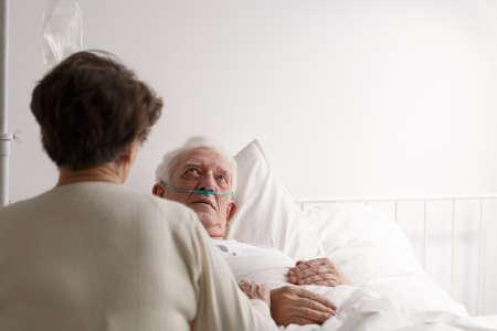 病院のベッドで座っている瀕死の夫を支えるシニアの妻 写真素材
