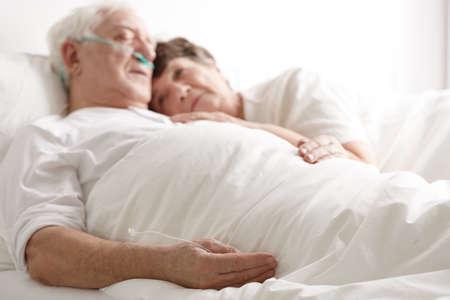 Lieve vrouw die ernstig zieke oudere man in het ziekenhuis koestert Stockfoto