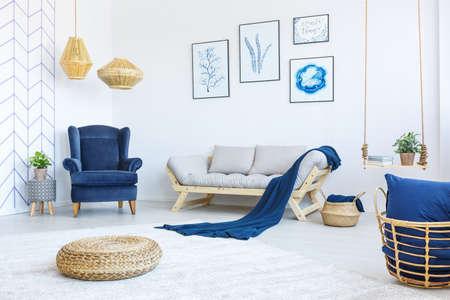 Nieuwe, witte woonkamer met blauwe leunstoel, bank, rotan poef