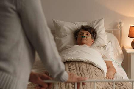 Stierende senior vrouw met haar ondersteunende liefdevolle echtgenoot thuis Stockfoto