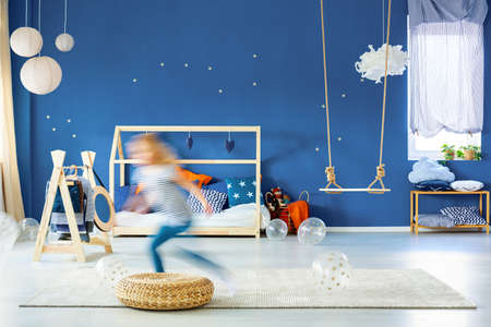 Child bedroom with navy blue wall, wood bed and swing