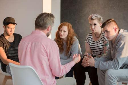 Consejero de adicción hablando con un grupo de sus pacientes adolescentes Foto de archivo - 78950019