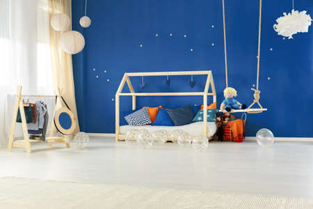 Child bedroom with diy wooden house bed and blue wall