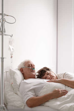 Sad wife lying next to sick dying husband in hospital bed