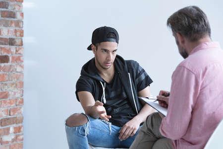 彼の心理学者と話しているキャップを身に着けている 10 代の少年