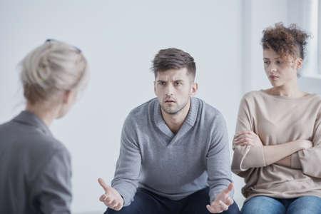 Boze jonge man en zijn verdrietige vrouw op een huwelijksterapie