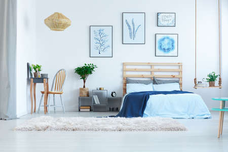 Beautiful, white bedroom with dressing table, bed and wall posters