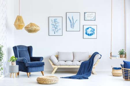 Biały i niebieski pokój dzienny z sofą, fotelem, lampą, plakatami