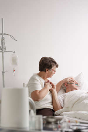 Elderly woman holding hand of sick dying husband in hospital