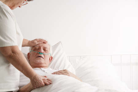 Caring loving wife supporting ill elderly husband in hospice Stock Photo
