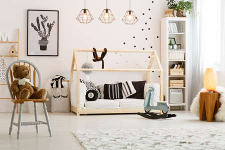 Modern designed wooden bed for baby in cozy spacious room
