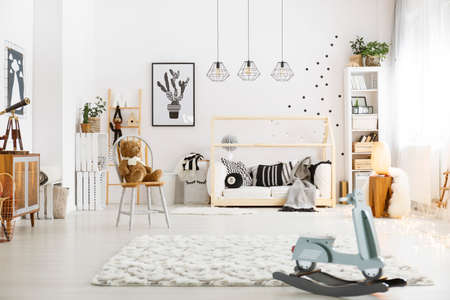 Spacious white baby room with white carpet and rocking horse