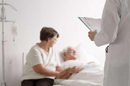 Ondersteunende vrouw van een diagnose van een oudere man die een arts luistert Stockfoto