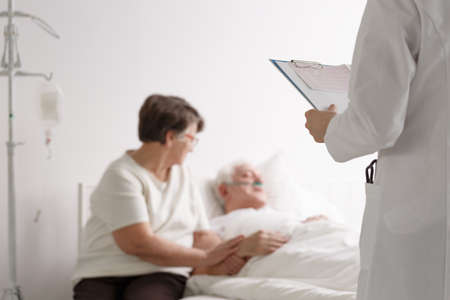 Supporting wife of an elderly man listening doctors diagnosis