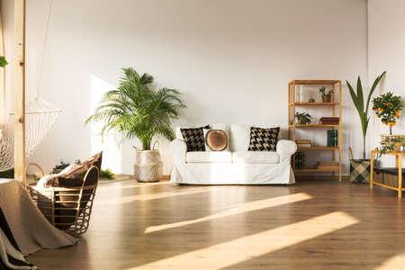 Open plan apartment with hammock, sofa, bookcase, plants, floor panels
