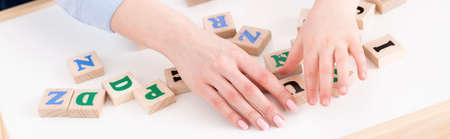 Nahaufnahme der Hand des Lehrers und des Mädchens, welche die Buchstaben setzt Standard-Bild - 78950551