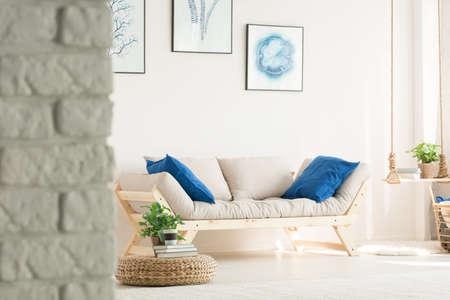 Stijlvolle, witte woonkamer met bakstenen muur, houten bank, posters
