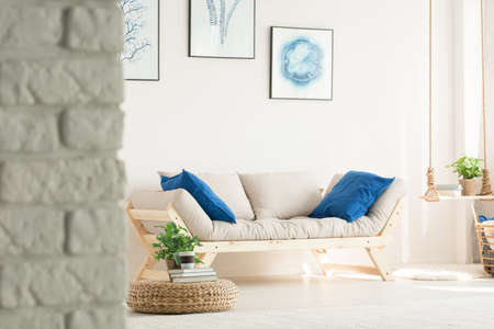 Stylish, white living room with brick wall, wood couch, posters