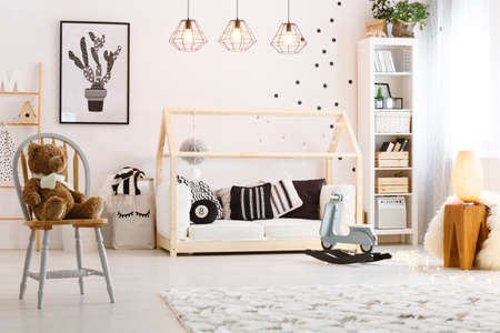 Cozy stylish baby room with rocking horse and teddy bear