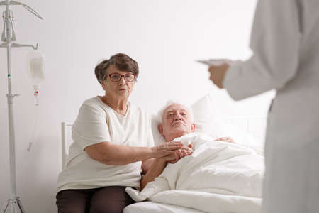 Elderly dying man lying in hospital with caring wife listening diagnosis