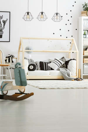 White and black pillows on the wooden bed in baby room Stock Photo
