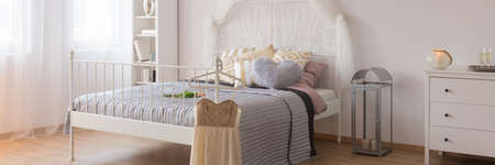 White stylish bed in white and grey cozy bedroom