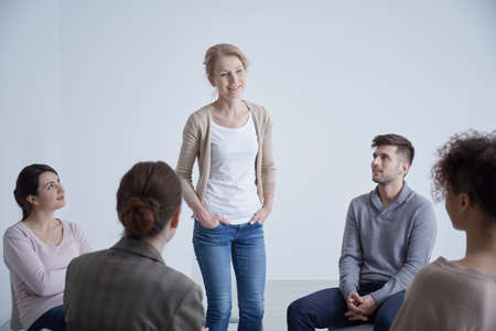 Young woman confessing her problem in a group