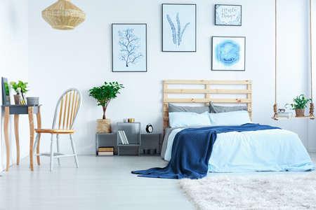 Lichte slaapkamer met kaptafel, stoel, bed, posters en lamp Stockfoto