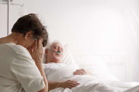 Depressed loving wife sitting by dying elderly husband in hospital